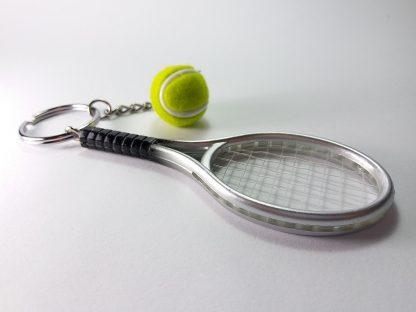 privezak za ključeve sivi reket i zelena lopta za tenis